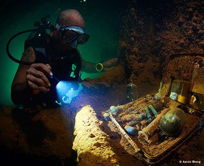 diver looking at artefacts in Truk Lagoon